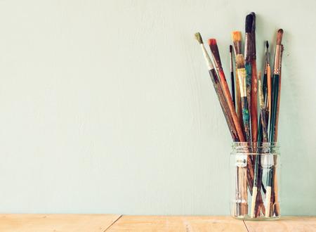 paint brushes in jar over wooden aqua blue background. vintage filtered image