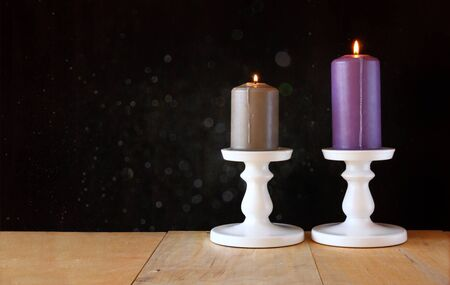 candelabra: image of Burning candle on wooden table and black textured background