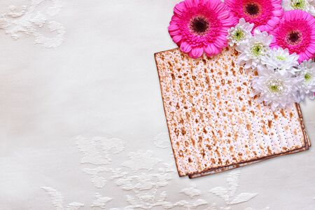 matzo: passover background. matzoh (jewish passover bread) and flowers on white table cloth