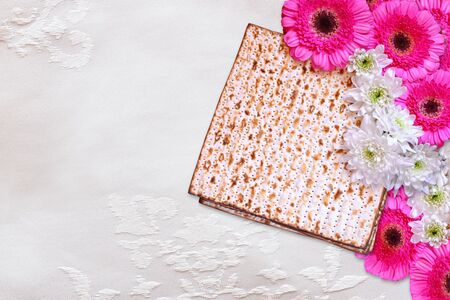 pesakh: passover background. matzoh (jewish passover bread) and flowers on white table cloth