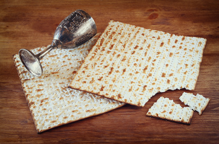 matzoth: Passover background. wine cup and matzoh (jewish passover bread) over wooden background. Stock Photo