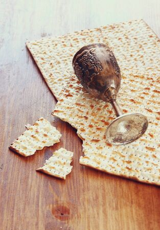 matzoh: Passover background. wine cup and matzoh (jewish passover bread) over wooden background. Stock Photo