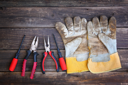 top view of worn work gloves and assorted work tools over wooden background photo