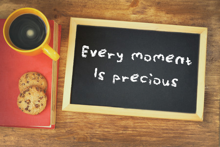 phrase: top view of blackboard with the phrase every moment is precious next to coffee cup over wooden table