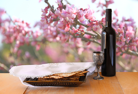 pesah: passover background. wine and matzoh (jewish passover bread) on wooden table