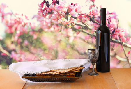 passover background. wine and matzoh (jewish passover bread) on wooden table