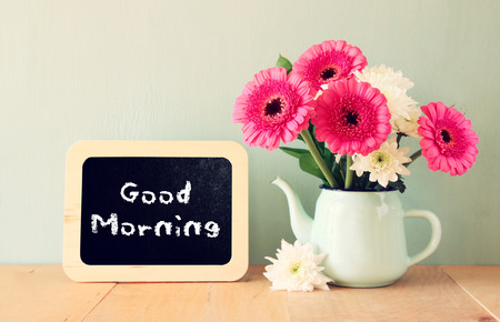 good: blackboard with the phrase good morning written on it next to vase with fresh flowers Stock Photo