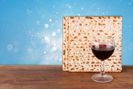 matzoth: passover background. wine and matzoh (jewish passover bread) over blue glitter background.