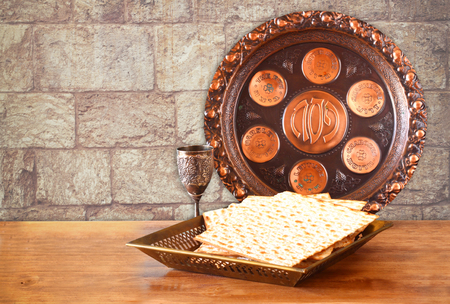 matzos: passover background. wine and matzoh (jewish passover bread) on wooden table and wall texture from jerusalem stone