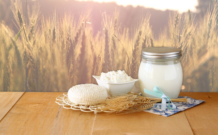 jewish: Tzfatit cheese , cottage and milk on wooden table over wheat field at sunrise sun burst background. jewish holiday Shavuot concept