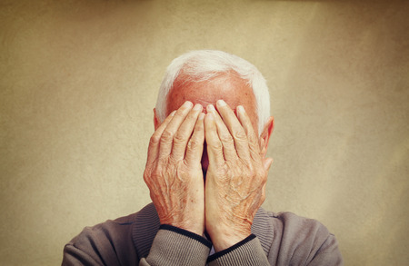 mid adult men: portrait of senior man covering his face with his hands