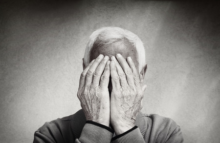 portrait of senior man covering his face with his hands. black and white image Stock Photo