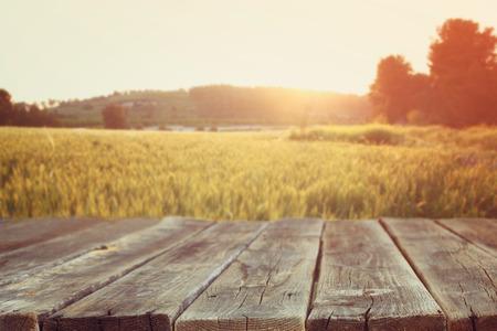paisaje de campo: mesa de tablero de madera en frente de campo de trigo en la luz del atardecer. Listo para montajes de exposición de productos