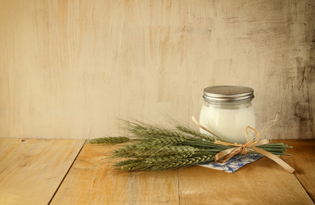 Jug of milk on wooden table over wooden textured background. Symbols of jewish holiday - Shavuot