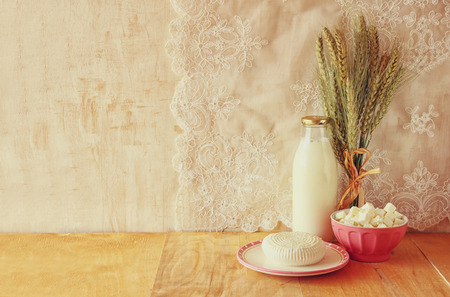 shavuot: greek cheese , bulgarian cheese and milk on wooden table over wooden textured background. Symbols of jewish holiday - Shavuot