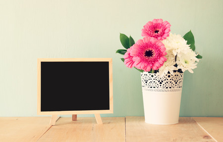 room for text: summer bouquet of flowers on the wooden table and blackboard with room for text with mint background. vintage filtered image Stock Photo