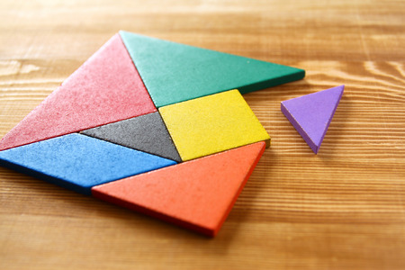 missing: a missing piece in a square tangram puzzle, over wooden table. Stock Photo