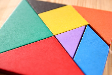 parallelogram: a missing piece in a square tangram puzzle, over wooden table. Stock Photo