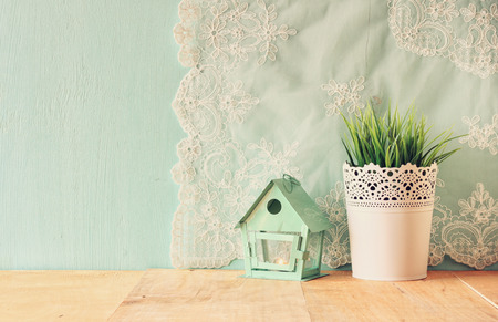 wood shelf: vintage Flower pot and lantern as a bird house against mint wall and antique lace fabric