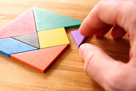 木製のテーブルの上の正方形のタングラム パズルの行方不明の部分。 写真素材