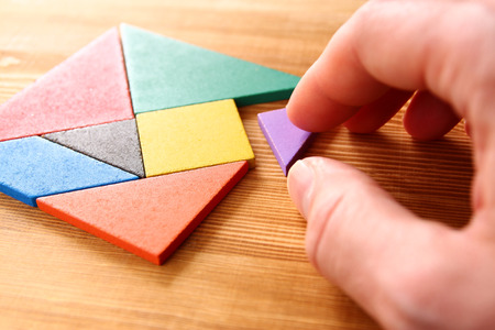 puzzle background: a missing piece in a square tangram puzzle, over wooden table. Stock Photo