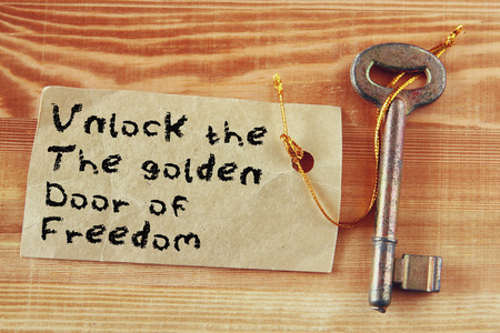 key to freedom: the phrase - unlock the golden door of freedom written on note attached to key