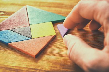 una pieza que falta en un rompecabezas tangram cuadrado, sobre la mesa de madera. Foto de archivo