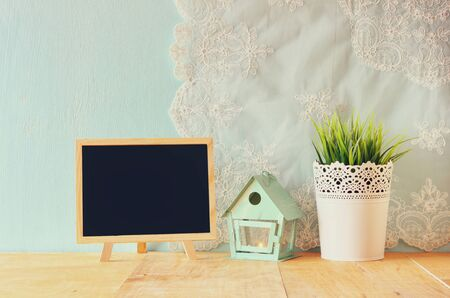 living thing: blackboard with room for text, vintage Flower pot and lantern as a bird house against mint wall and antique lace fabric
