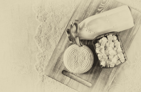 dairy product: image of greek cheese , bulgarian cheese and milk on wooden table over wooden textured background. Symbols of jewish holiday - Shavuot. Black and white style photo