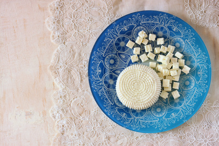 shavuot: top view of greek cheese and bulgarian cheese on wooden table over wooden textured background. Symbols of jewish holiday - Shavuot
