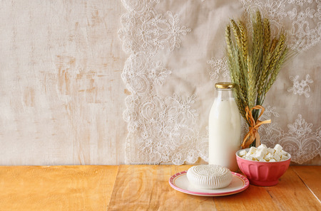 shavuot: greek cheese and milk on wooden table over wooden textured background. Symbols of jewish holiday - Shavuot