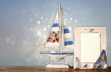 Vintage Nautical Frame With Wooden Boat On Wooden Table And Glitter ...