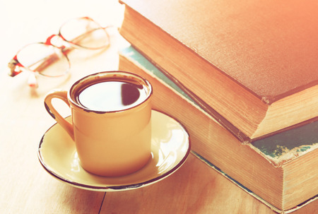 coffee cup, stack of old books and reading glasses over wooden table. selective focus, retro style image