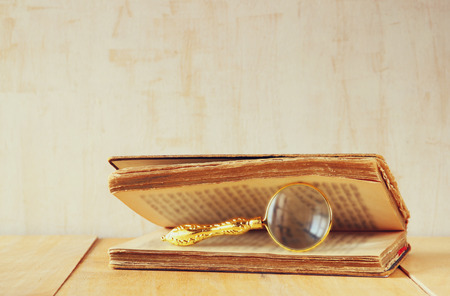 macro image of magnifying glass over antique open book. photo