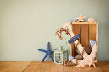 ancre marine: ancre en bois, poissons d'étoile et la lanterne sur la table en bois. image vintage filtrée Banque d'images
