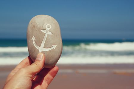 man hand holding one stone pebbles with the anchor sign  against sandy beach and sea horizon Stockfoto