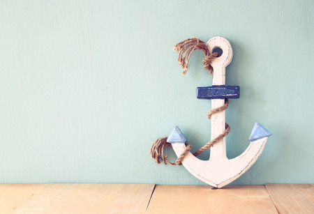 element old: old nautical anchor on wooden table over wooden aqua background