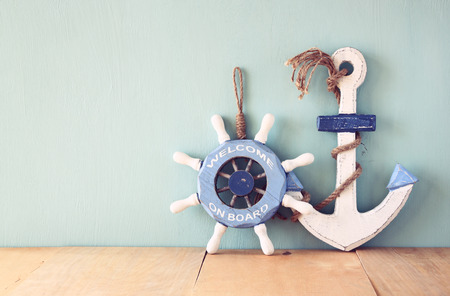 old nautical wood wheel, anchor on wooden table over wooden background. vintage filtered image