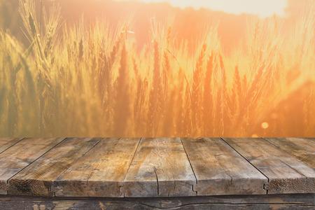 Houten bord tafel in de voorkant van het veld van tarwe op zonsondergang licht. Klaar voor product-display montages