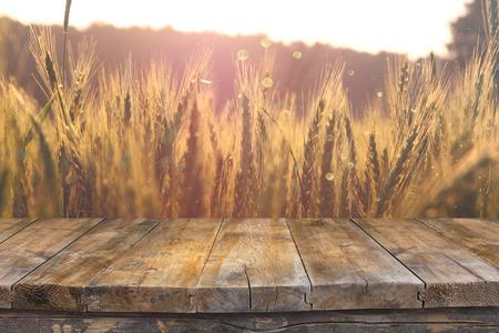 日没の光の小麦畑の前に木板テーブル。製品表示モンタージュの準備ができて