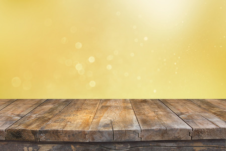 front desk: Rustic wood table in front of glitter green and gold bright bokeh lights