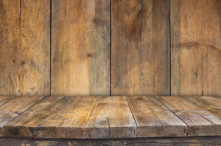 Grunge vintage wooden board table in front of old wooden background. Ready for product display montages