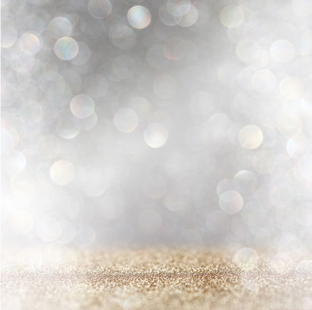 defocused: abstract image of glitter vintage lights background with light burst . silver, gold and white. de-focused.