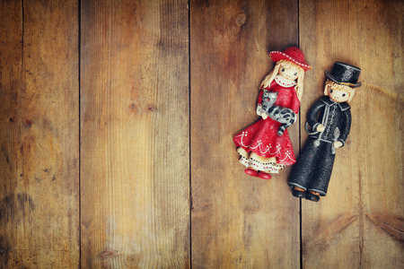 wooden doll: A beautiful vintage old pair dolls over a wooden background