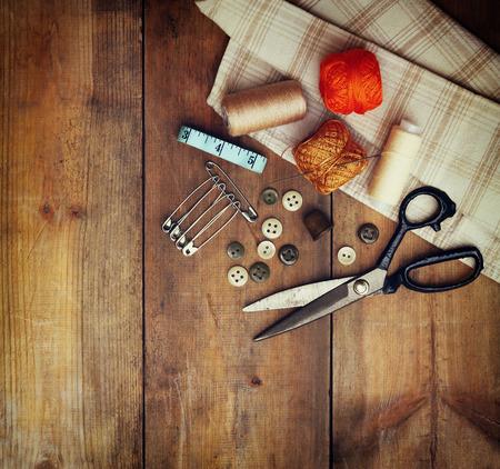 나무 질감 배경 위에 바느질 도구 및 재봉 키트와 빈티지 배경