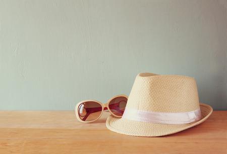 페도라 모자와 나무 테이블 위에 선글라스. 휴식 또는 휴가 개념 스톡 콘텐츠