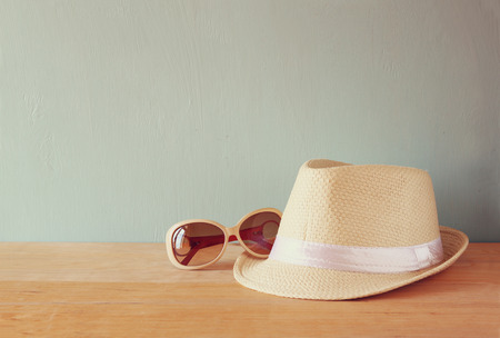 fedora hat: fedora hat and sunglasses over wooden table. relaxation or vacation concept