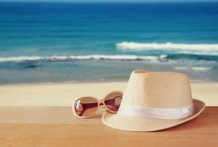 sunglass: fedora hat and stack of books over wooden table and sea landscape background. relaxation or vacation concept