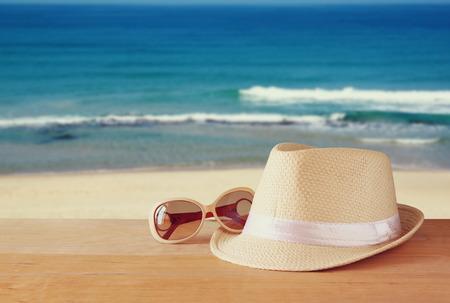anteojos de sol: sombrero de fieltro y la pila de libros sobre la mesa de madera y fondo del paisaje del mar. relajación o vacaciones concepto