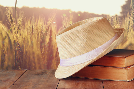 fedora: fedora hat and stack of books over wooden table and field of wheat country side background. relaxation or vacation concept